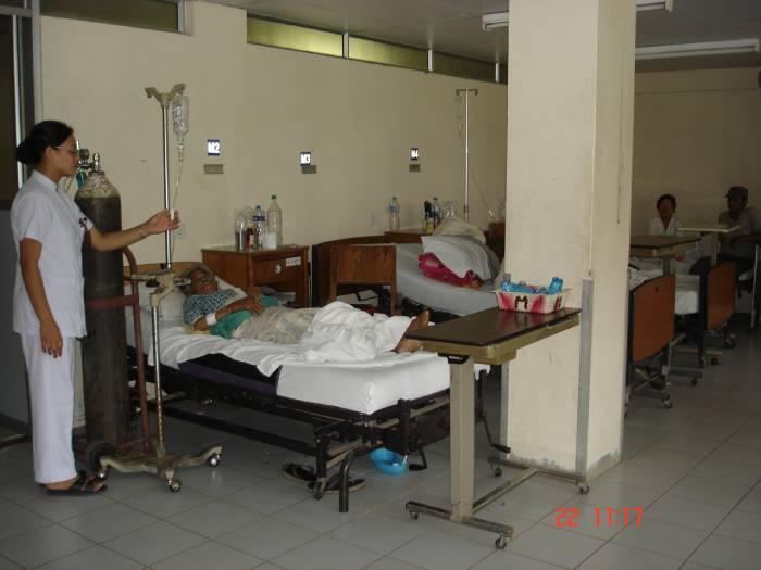 Student adjusting medications at patient_s bedside